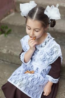 Een klein meisje in een schooluniform dat snacks eet