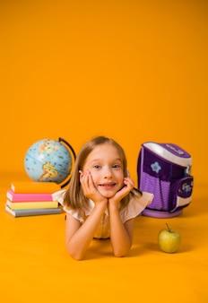 Een klein meisje in een schooluniform ligt op de vloer met schoolspullen op een gele achtergrond met een plek voor tekst