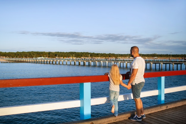 Een klein meisje in een spijkerbroek en een t-shirt met haar vader staat op een pier bij de oostzee
