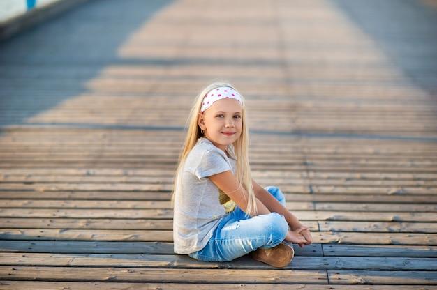 Een klein meisje in een spijkerbroek en een t-shirt zit op een pier in de buurt van de oostzee