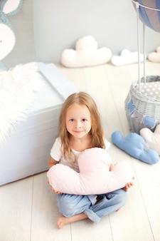 Een klein meisje in een t-shirt en spijkerbroek houdt een wolkkussen tegen de muur van een decoratieve ballon. toddler speelt in de kinderkamer. het concept van kindertijd, reizen. interieur kamer