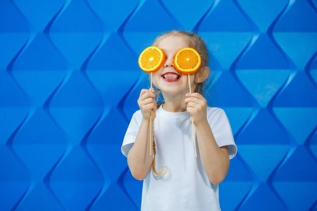 Een klein meisje in een t-shirt glimlacht en houdt twee helften oranje fruit voor haar ogen op een blauwe achtergrond. concept: de strijd tegen avitomnosis in de lente.