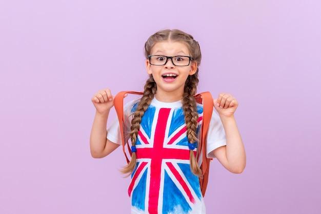 Een klein meisje in een t-shirt met een afbeelding van de engelse vlag op een geïsoleerde paarse achtergrond. vreemde talen leren.