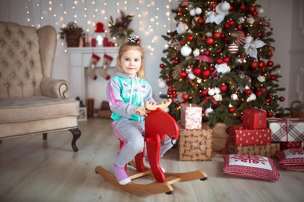 Een klein meisje in een trainingspak zit op een houten rode elandschommelstoel in de buurt van een kerstboom.