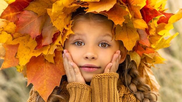 Een klein meisje in een trui en een esdoornkrans op haar hoofd in de herfst.