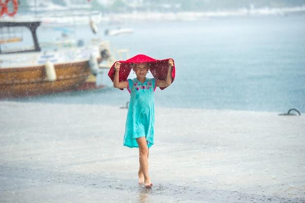 Een klein meisje in een turquoise jurk loopt in de regen op de dijk in turkije
