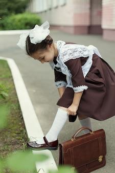 Een klein meisje in een vintage uniform met een koffertje staat naast de school en trekt haar witte kniekousen omhoog