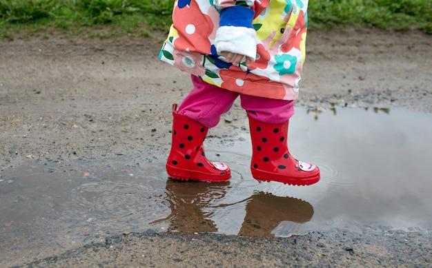 Een klein meisje in een vrolijk jasje en rode laarzen springt vrolijk door plassen. lente gevoel.