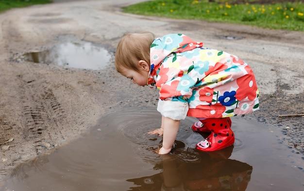 Een klein meisje in een vrolijk jasje en rubberen laarzen speelt vrolijk in een lentepoel. geluk van kinderen.