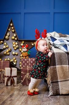 Een klein meisje in een warme trui zit onder een kerstboom met speelgoed en geschenken met hoorns op haar hoofd. gelukkige jeugd. nieuwjaars vakantie sfeer