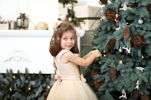 Een klein meisje in een weelderige beige jurk hangt kegels aan de kerstboom die in het huis staat.