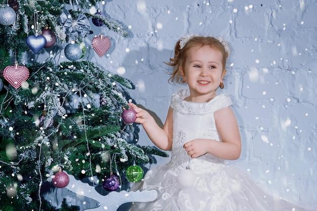 Een klein meisje in een weelderige jurk versiert de kerstboom voor het nieuwe jaar