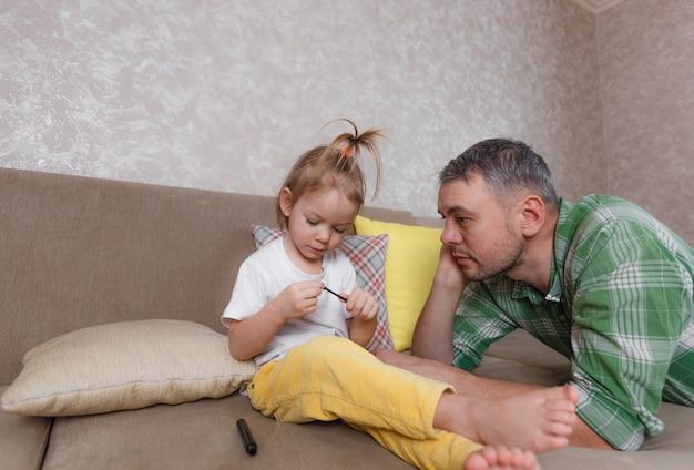 Een klein meisje in een wit t-shirt en een gele broek speelt met haar vader thuis op de bank