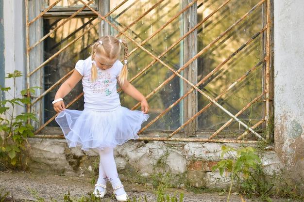 Een klein meisje in een wit t-shirt en rok leert dansen op straat bij het raam van een oud huis