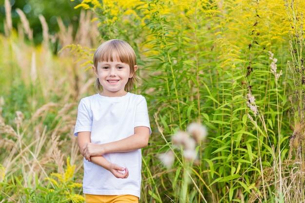 Een klein meisje in een wit t-shirt staat tussen de gele herfstbloemen in het veld en glimlacht.