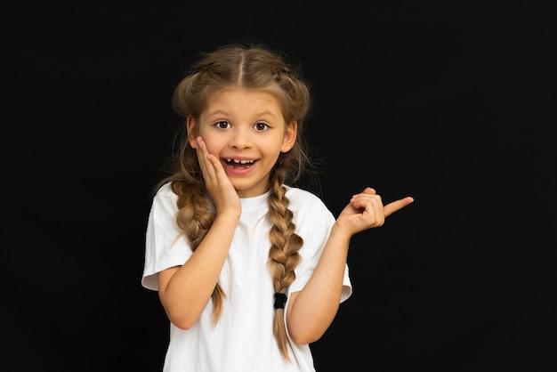 Een klein meisje in een wit t-shirt toont verbazing.