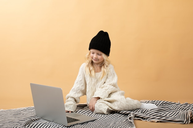 Een klein meisje in een witte gebreide jurk en een zwarte hoed zit op een plaid op een gele.