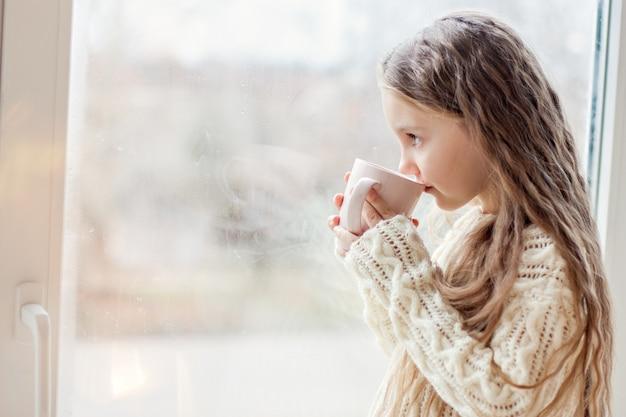 Een klein meisje in een witte gebreide trui drinkt warme chocolademelk, cacao