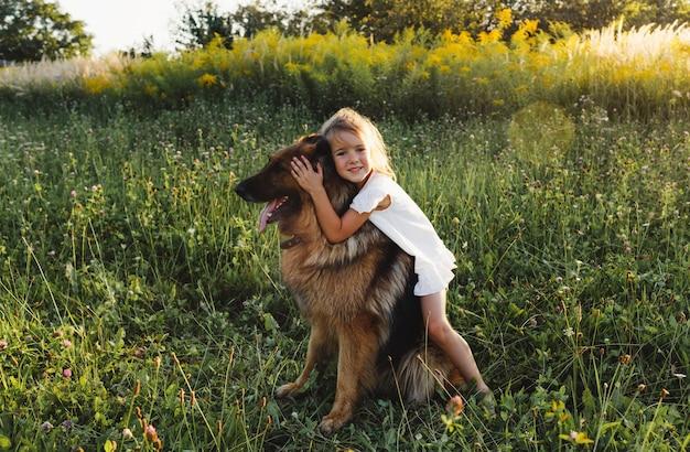 Een klein meisje in een witte jurk knuffelt een grote duitse herdershond die op het groene gras staat. kinderspellen met een hond.