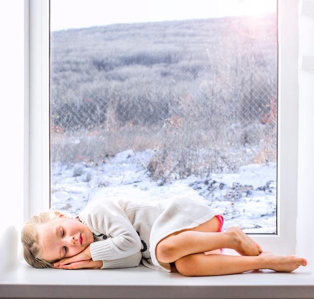 Een klein meisje in een witte jurk zit bij het raam en kijkt naar het winterbos