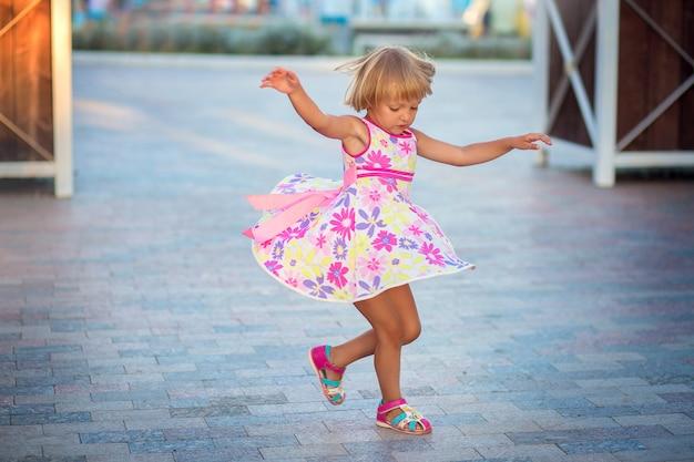 Een klein meisje in een zomerjurk dansen op straat op het stadsplein. het kind draait en vliegt in een zomerjurk