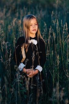 Een klein meisje in een zwarte jurk staat in hoog gras en houdt een groen boek vast terwijl ze naar de zonsondergang kijkt.