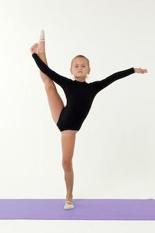 Een klein meisje in een zwarte turnpakje voert een oefening uit