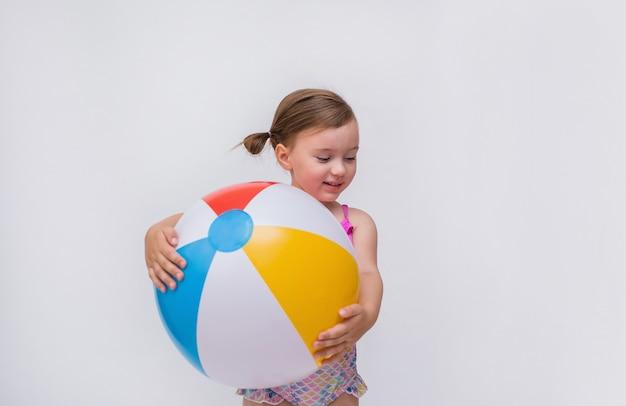Een klein meisje in een zwempak met een opblaasbare bal op een geïsoleerd wit