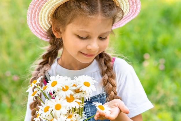 Een klein meisje in het dorp bewondert madeliefjes.