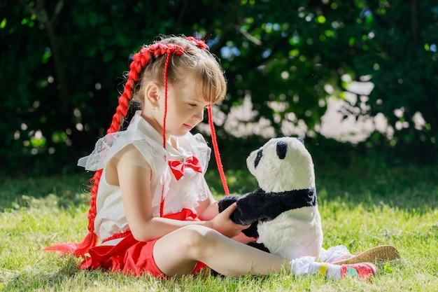 Een klein meisje in het park in de zomer zittend met een speelgoedpanda. hoge kwaliteit foto