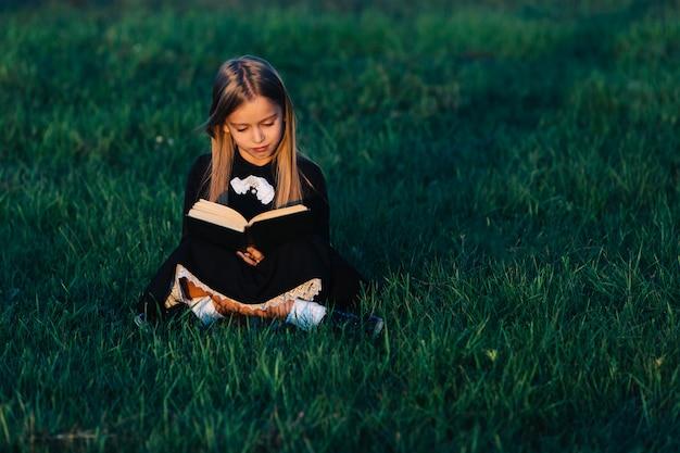 Een klein meisje in het zwart zit op het gras en houdt een groen boek in het licht van de ondergaande zon. een kind leest buiten in de natuur.