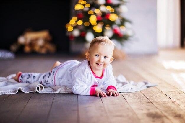 Een klein meisje in kerstpyjama lacht tegen de achtergrond van een boom en een open haard. hoge kwaliteit foto