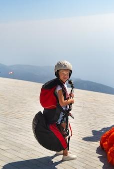 Een klein meisje in paragliding-uitrusting en met een camera staat aan de rand van de berg babadag.turkije