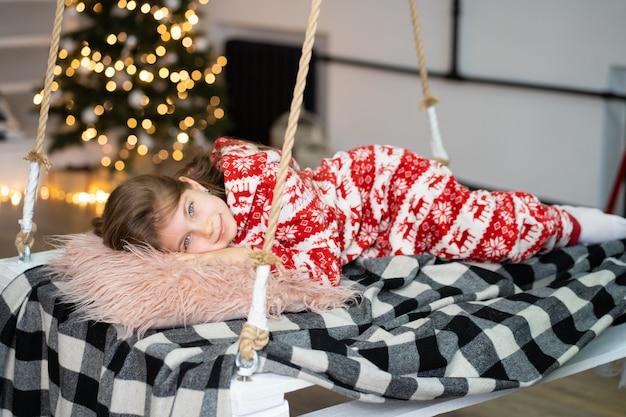 Een klein meisje in pyjama kan niet slapen op een feestelijke avond