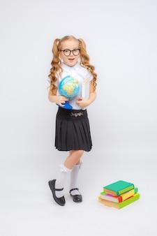 Een klein meisje in schooluniform en glazen heeft een wereldbol in haar handen op een witte achtergrond