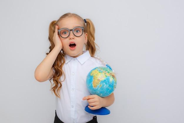 Een klein meisje in schooluniform en glazen met een wereldbol in haar handen past haar bril op een witte achtergrond aan