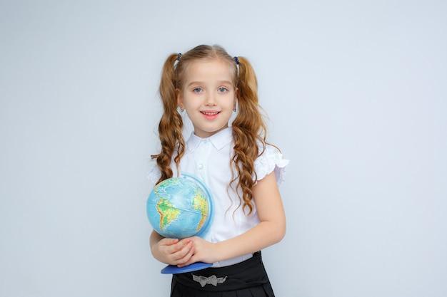 Een klein meisje in schooluniform heeft een wereldbol in haar handen op een witte achtergrond