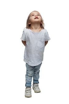 Een klein meisje in spijkerbroek staat op en kijkt op. kinderachtige nieuwsgierigheid. geïsoleerd op een witte achtergrond. verticaal.