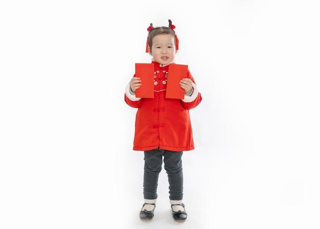 Een klein meisje in traditionele chinese kleding houdt een rode envelop voor het nieuwe jaar in haar hand