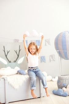 Een klein meisje in vrijetijdskleding houdt een wolkkussen tegen de muur van een decoratieve ballon. het kind speelt in de kinderkamer. het concept van kindertijd. verjaardag, vakantie decoraties