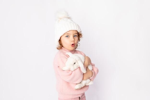 Een klein meisje in winterkleren houdt een konijn vast op een witte achtergrond. nieuwjaarsconcept, ruimte voor tekst