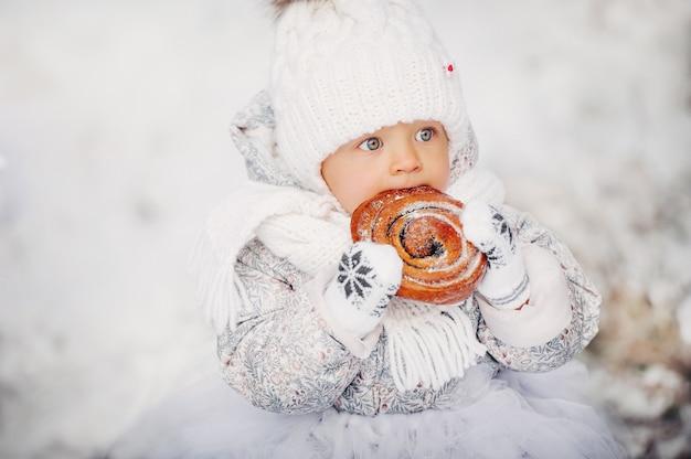 Een klein meisje in witte kleren in de winter op straat die een broodje eet.