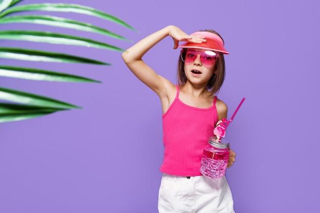 Een klein meisje in witte korte broek een roze tshirt roze trendy bril met een drankje in de hand en een zomerse vi...