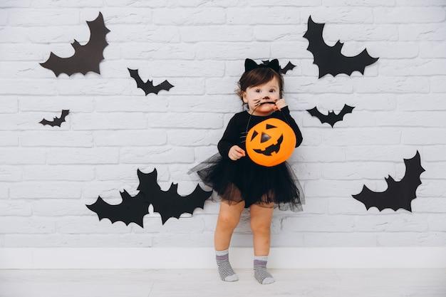 Een klein meisje in zwarte kat kostuum bijt pompoen mand