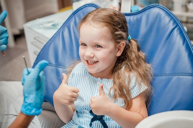 Een klein meisje is blij met het einde van de behandeling bij de tandarts