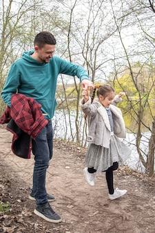 Een klein meisje is een werveling en houdt de hand van haar vader vast voor een wandeling in het bos.