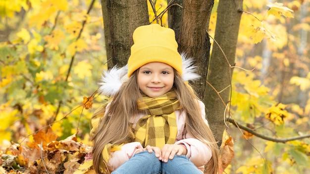 Een klein meisje is in het bos tussen de gevallen herfstbladeren.