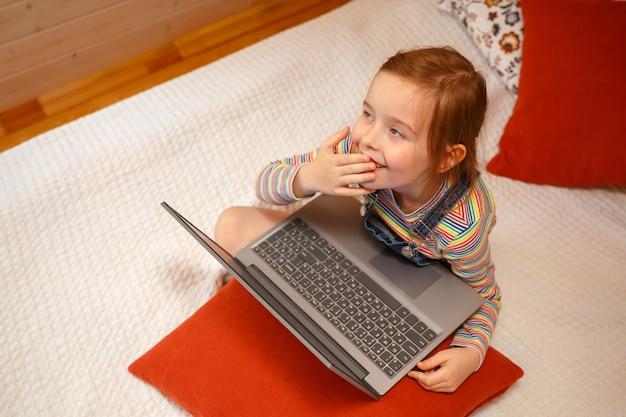Een klein meisje kijkt met verschillende emoties naar de computer. meisje speelt op een computer