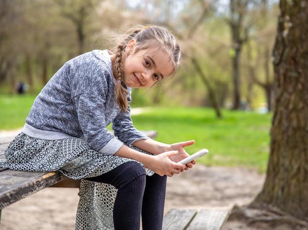 Een klein meisje kijkt op haar telefoon en let niet op de prachtige natuur rondom.