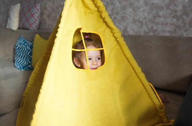 Een klein meisje kijkt tijdens het spelen uit het raam van een gele tipi